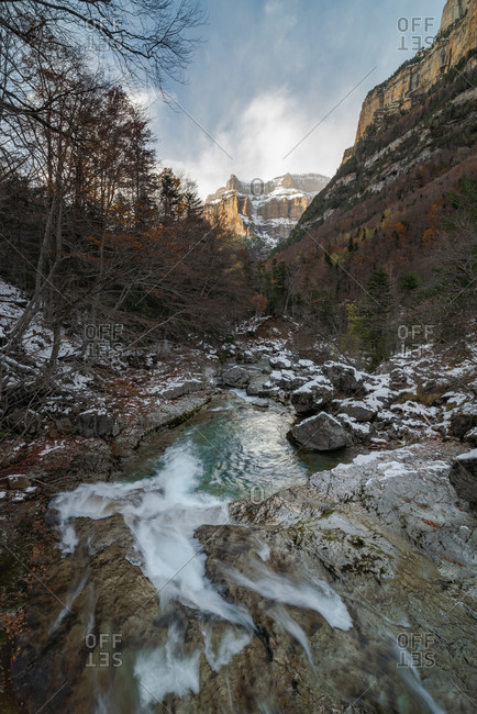 Amazing natural landscape of rapid shallow river streaming among boulders in mountainous terrain with forest and rocky peak in background in cloudy autumn day