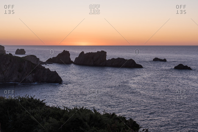 Amazing tranquil scenery of rippled sea water and dark rocky formations under colorful sunset sky in summer evening