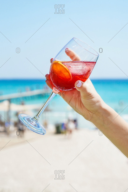 Unrecognizable female holding wineglass of refreshing citrus alcoholic cocktail while chilling on sunny beach in summertime
