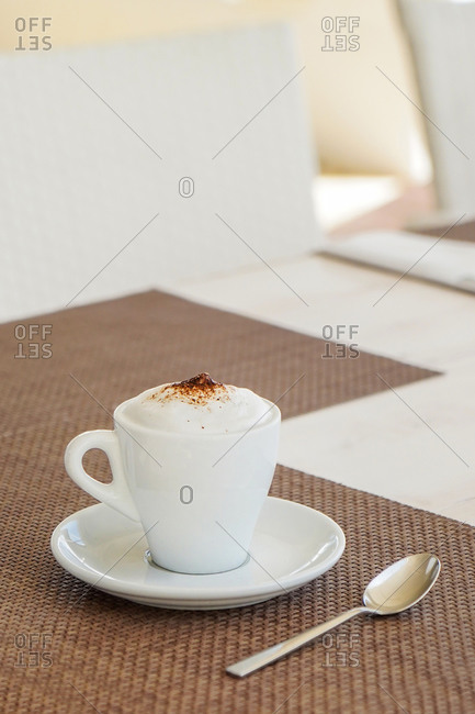 Served white ceramic cup with fresh coffee topped with milk froth and placed on wicker mat on restaurant table