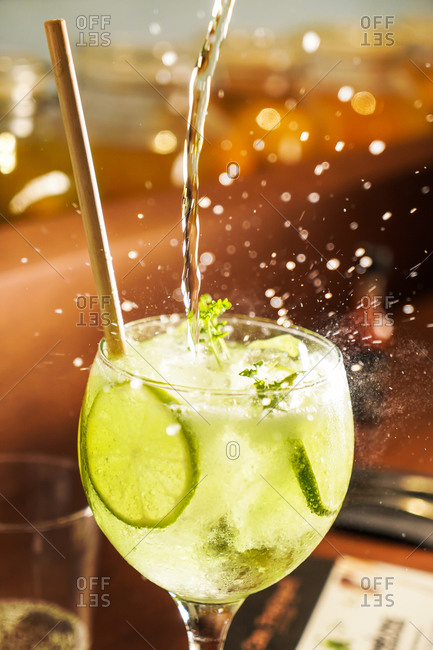 Splashing flow of alcoholic mojito cocktail in crystal glass with lime slices and straw in sunlight