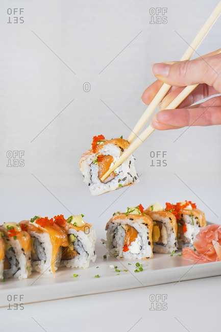 From above faceless woman holding sushi with chopsticks above white wooden table