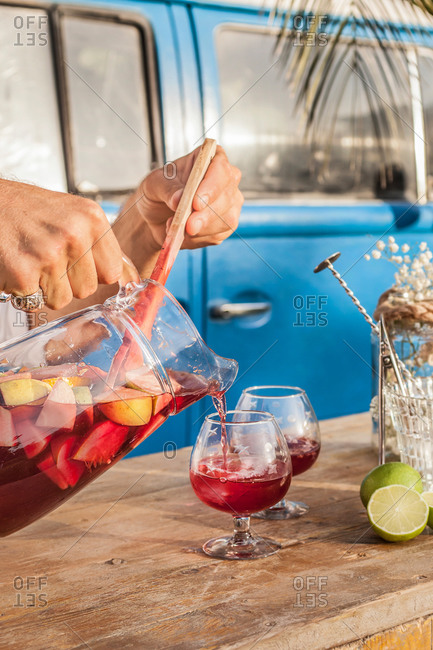 Faceless person pouring cool sangria in crystal glasses on wooden table against blue van on tropical beach