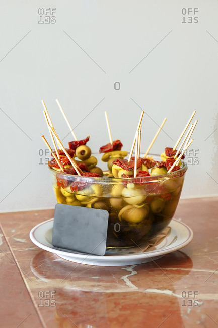 Bowl with pickle water filled with skewers of green olives and salami served on plate with small blackboard card