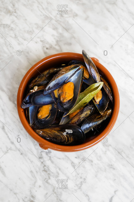 Top view of round bowl filled with freshly cooked mussels with greens placed on marble table