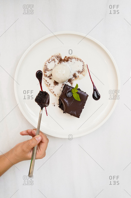 Top view of faceless person having bite of chocolate square cake with ganache and ice cream