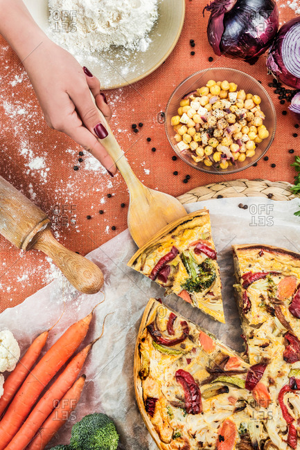Overhead of faceless woman having piece of veggie quiche on table with bowl of chickpea and ingredients