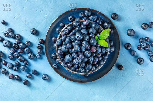 Fresh blueberries with green leaves, shot from above