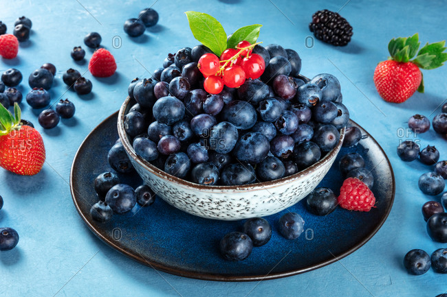 Fresh blueberries, red currants and strawberries with green leaves