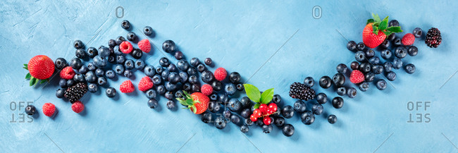 A vegan panorama of fresh summer food. Blueberries, raspberries, strawberries and red currants, shot from the top