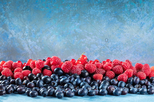 Fresh blueberries, redcurrants and raspberries texture, side view with a place for text