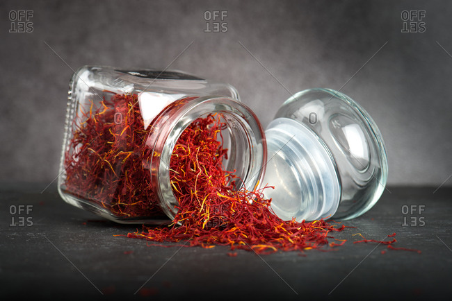 Aromatic dried saffron sprinkled from glass jar on table on gray background in studio