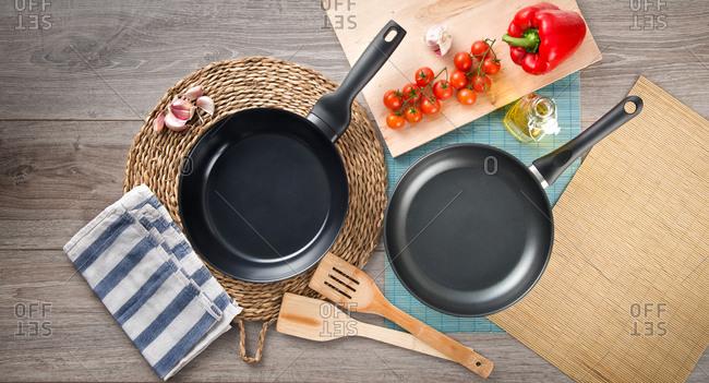 Modern frying pans above ground in studio