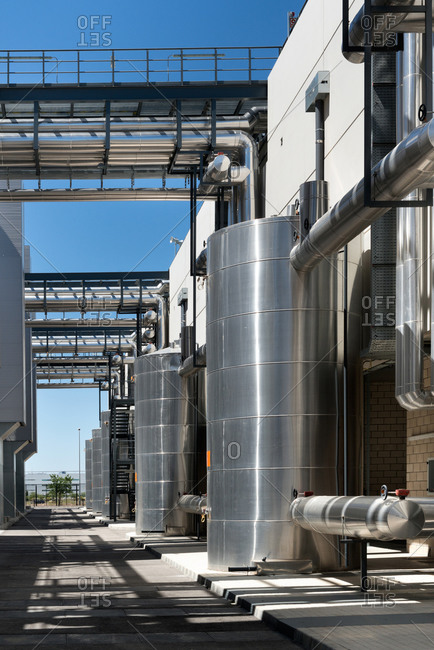 Asphalt walkway going through contemporary factory with metal tanks on background of blue sky