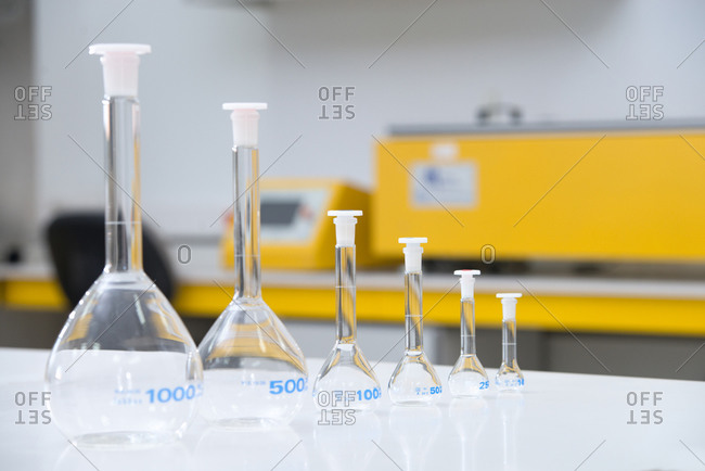 Various glass flasks placed in row on table and prepared for experiments in modern laboratory