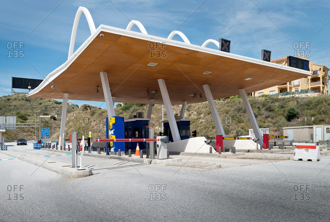 Futuristic exterior of toll road with contemporary payment system on background of blue sky