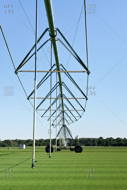 Vehicle with stainless steel construction with hanging tubes on lawn with smooth surface near forest under serene sky in daylight