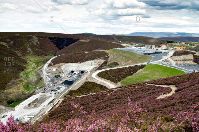 Amazing highland landscape with flower meadows and construction site with machinery against cloudy sky