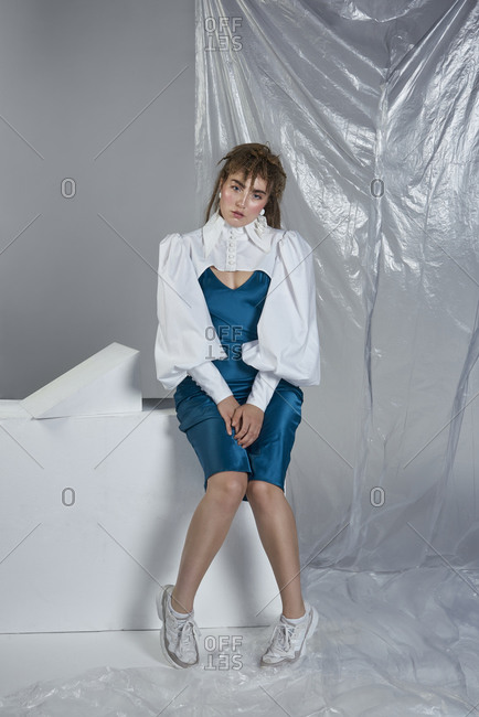 Stylish young woman in formal dress and short jacket with lush sleeves siting near crumpled plastic and looking at camera