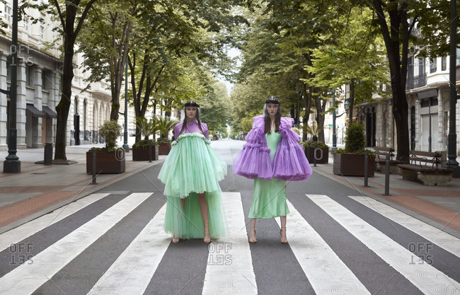 Full body fashionable female models wearing creative designers chiffon dresses of bright green and purple colors and standing on street pedestrian crossing