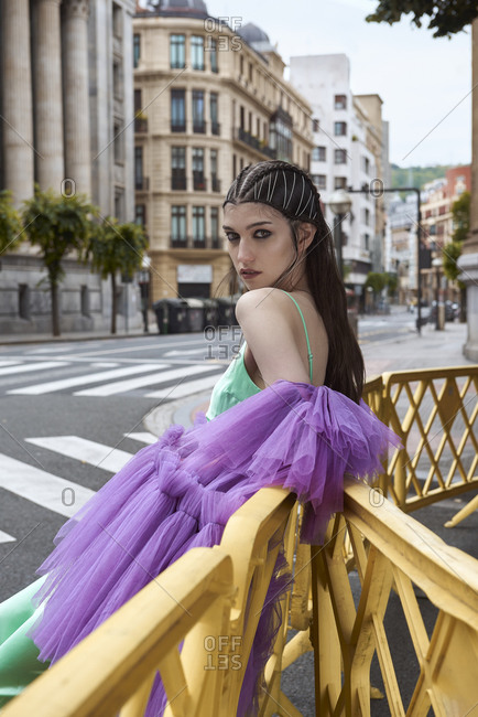 Side view unemotional fashionable lady posing in haute couture gown of green and purple colors while leaning on railing on street