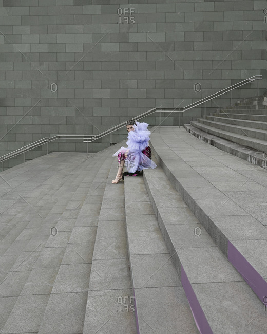Full body side view young female model wearing fashionable chiffon outfit of lilac color sitting on street staircase and looking at camera
