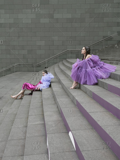 Full body side view young females model wearing fashionable chiffon outfit of lilac color sitting on street staircase