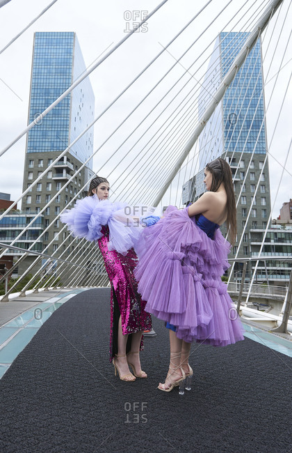 Gorgeous young females in fashionable dresses with paillettes of purple and lilac colors wearing protective latex gloves while modeling standing on urban path with road cones looking at each other holding hands