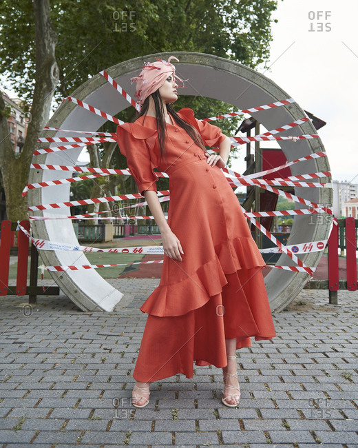 Full body emotionless female model in trendy maxi red dress and stylish headwear posing against urban background and looking away