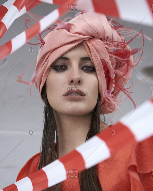 Stylish young female wearing fancy red dress and creative pink turban standing amidst red and white cordon tape looking at camera