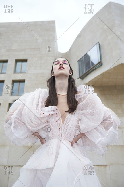 From below gorgeous young female model posing in fashionable haute couture light pink dress with hand on waist while standing on street