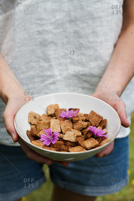 Unrecognizable female with ceramic bowl full of yummy cinnamon cereal on sunny day in countryside