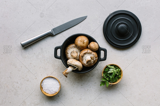 Top view of fresh champignons in saucepan placed on table with salt and parsley in kitchen
