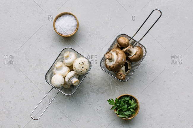 From above of raw mushrooms placed in metal containers on table near bowls with salt and greenery