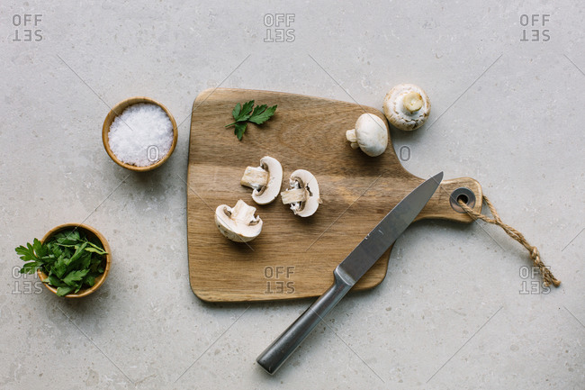 From above of raw mushrooms placed in wooden cutting board on table near bowls with salt and greenery