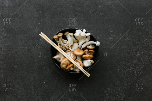 Top view of bowl with various raw mushrooms placed on black table with chopsticks in kitchen