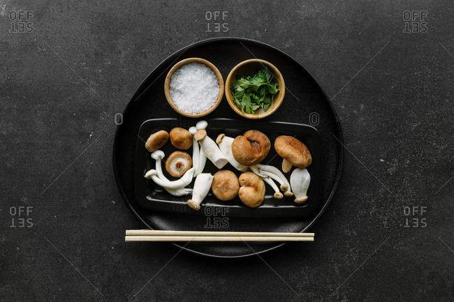Top view of bowl with various raw mushrooms placed on black table with chopsticks in kitchen near salt and parsley