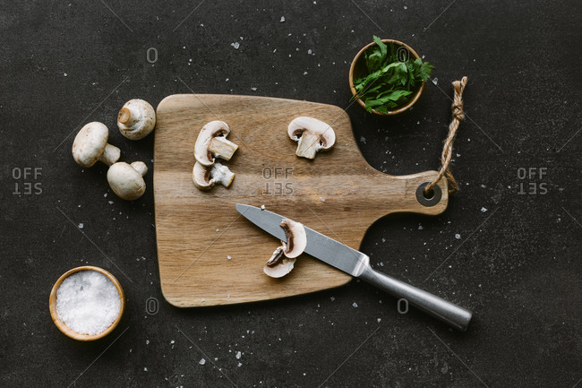 From above of raw mushrooms placed in wooden cutting board on table near bowls with salt and greenery on dark background