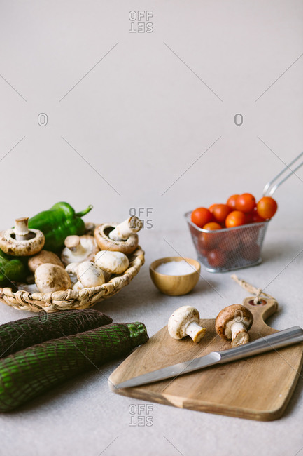 Ripe vegetables and raw mushrooms placed on wooden cutting board in a table in kitchen for healthy lunch
