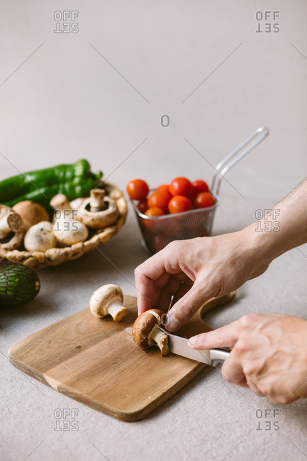 Cropped unrecognizable person hand cutting raw mushrooms on wooden chopping board near fresh vegetables in a table in kitchen for healthy lunch