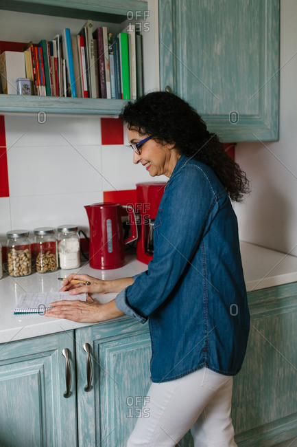 Senior woman reading recipe's notes for cooking