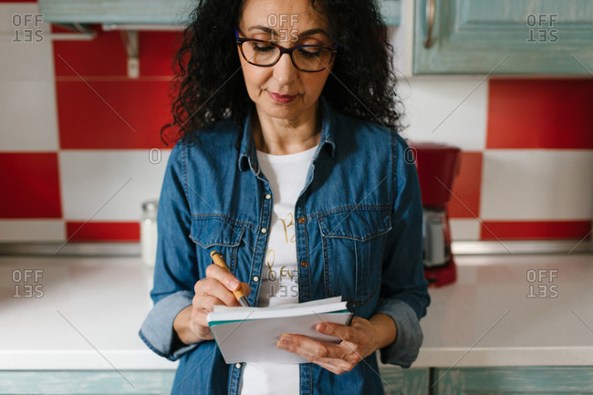 Close-up view of a senior ethnic woman taking notes about recipes