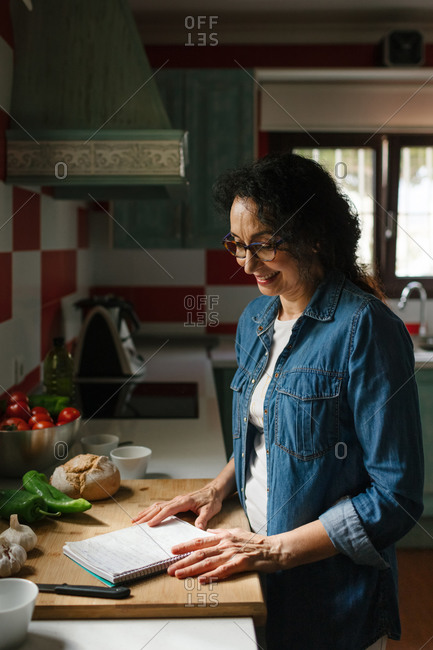 Happy senior woman in the kitchen reading some recipes with food to prepare
