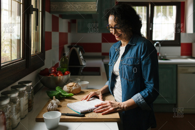 Smiley senior woman with recipe's notes and veggie food in the kitchen