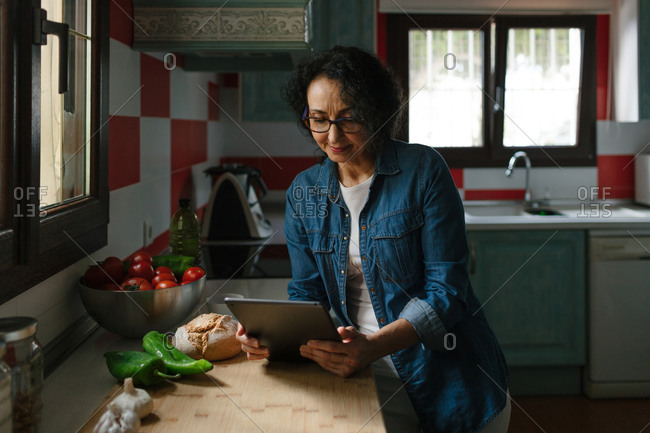 Senior woman looking for recipes on a tablet in the kitchen