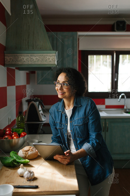Happy woman looking for recipes on a tablet in the kitchen
