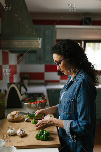 Woman chopping peppers in the kitchen for making typical Spanish food.