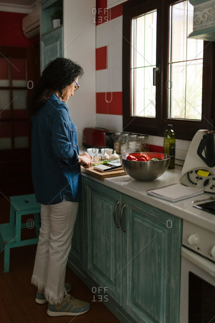 Middle-age woman preparing a Salmorejo in her kitchen.