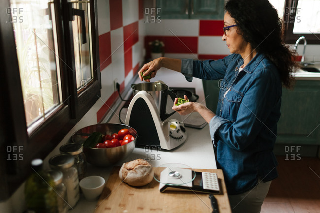 Woman introducing some ingredients in a kitchen robot