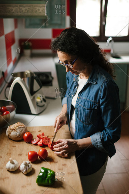 Senior woman chopping some tomatoes for making Salmorejo, typical Spanish food